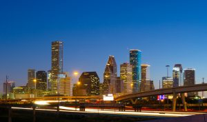 Houston downtown skyline at dusk in a backlit scene with a highway including light trails in the foreground.
